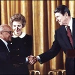 Milton Friedman (left) shakes is greeted by President Ronald Reagan and first lady Nancy Reagan (The Washington Post)